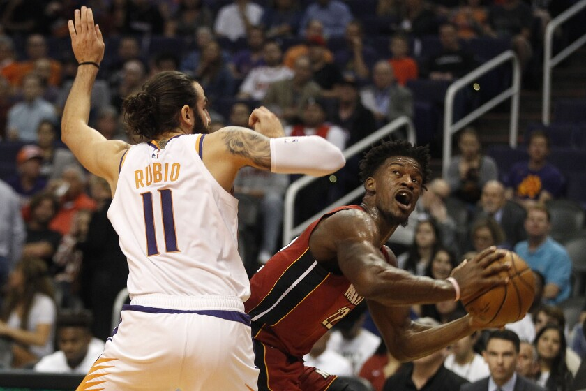 Miami Heat's Jimmy Butler (22) looks to the basket against Phoenix Suns' Ricky Rubio (11) during the first half of an NBA basketball game Thursday, Nov. 7, 2019, in Phoenix. (AP Photo/Darryl Webb)