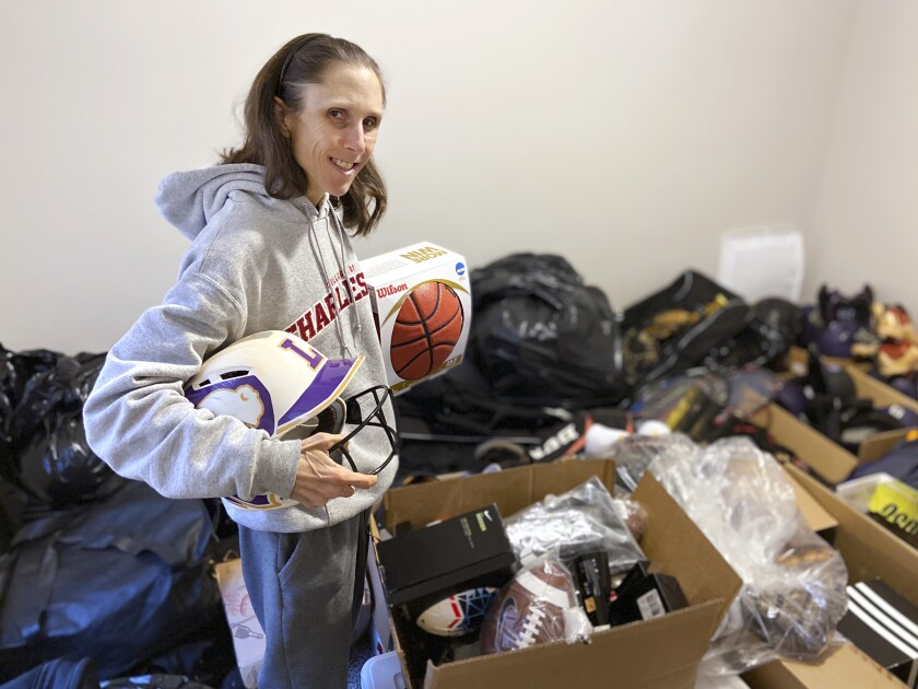 Rhiannon Potkey displays sports equipment Jan. 30, 2021, in Knoxville, Tenn. Goods4Greatness, the nonprofit started by Potkey, works to get much-needed gear to low-income children and teens to make sure the high cost of equipment doesn't stop their athletic dreams. (AP Photo/Teresa Walker)