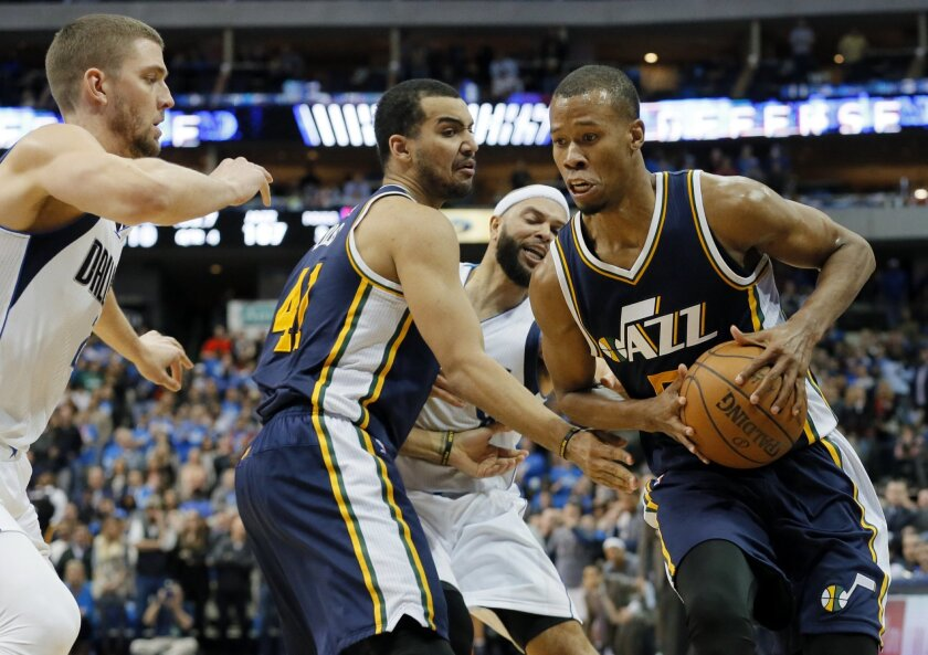 Dallas Mavericks' Chandler Parsons, left, defends as Utah Jazz's Rodney Hood (5) sprints to the corner to take a 3-point shot that would sink late in the second half of an NBA basketball game, Tuesday, Feb. 9, 2016, in Dallas. The shot tied up the game sending it into overtime where the Jazz won 12
