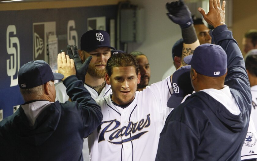 The Padres' Yasmani Grandal celebrates in the dugout with teammates after he hit a home run in the eighth inning.