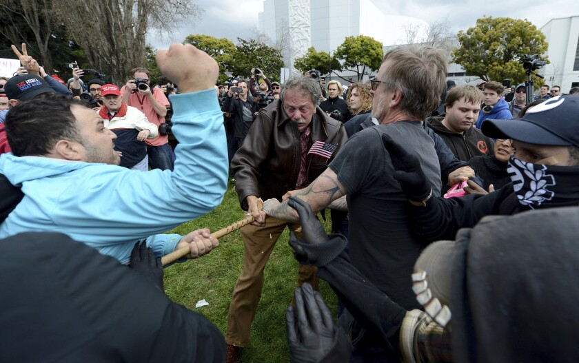 Counter-protesters try to take a large piece of wood away from a participant in a rally in support o