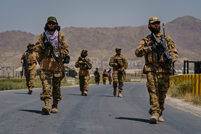 Several Taliban fighters in uniform carry weapons.