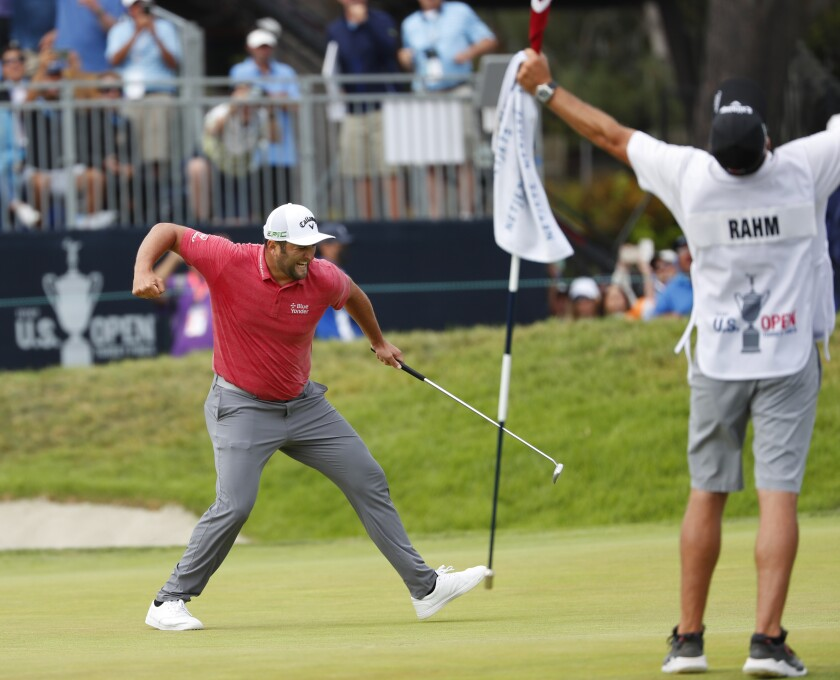 Jon Rahm celebrates with caddy Adam Hayes after sinking a birdie putt on the 18th hole as he won the US Open in La Jolla.