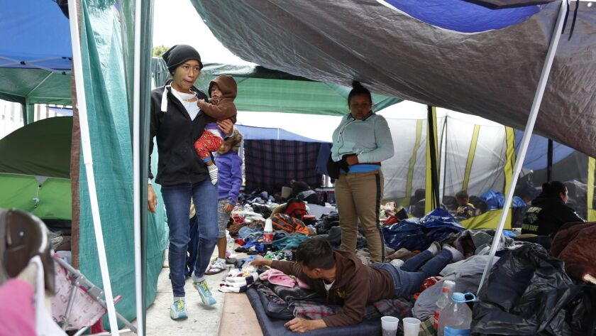 Central Americans seeking asylum deal with overnight rain conditions at the Chaparral USA/Mexico pedestrian border.