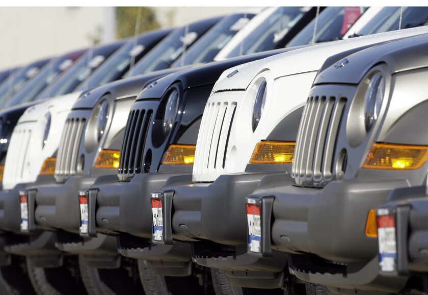 FILE- In this Sunday, Oct. 22, 2006, file photo, a long line of unsold 2006 Jeep Libertys sit on the back lot of a Chrysler Jeep dealership in the southeast Denver suburb of Centennial, Colo.  An auto safety advocate is calling on the government to reopen an investigation of rear-crash fires in old