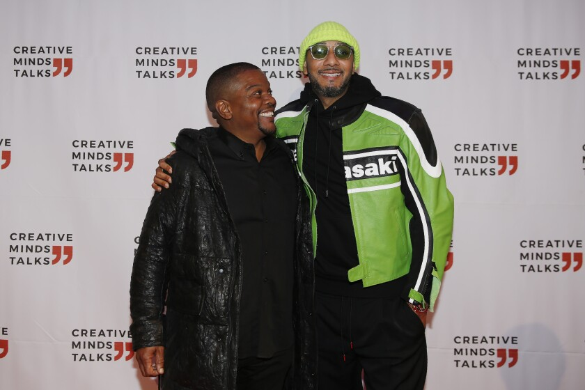 Kehinde Wiley and Swizz Beatz hug as they arrive during Art Basel, Monday, Dec. 2, 2019, in Miami Beach, Fla. (AP Photo/Brynn Anderson)