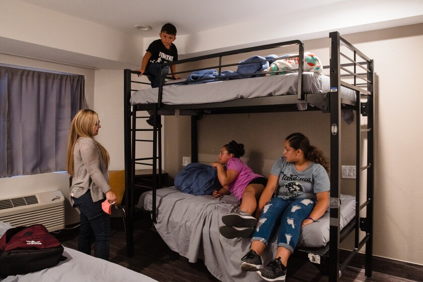 Erikssa Martinez, left, talks to her children, Adrian, Valerie and Alessa in their room at a city-run interim family shelter