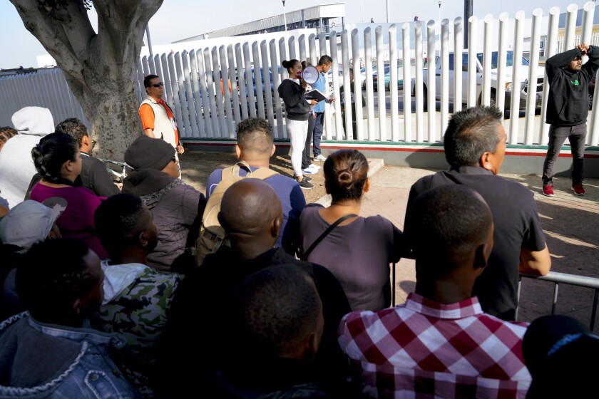 Asylum seekers wait in Tijuana by the port of entry while a woman holding a megaphone calls names from a notebook.