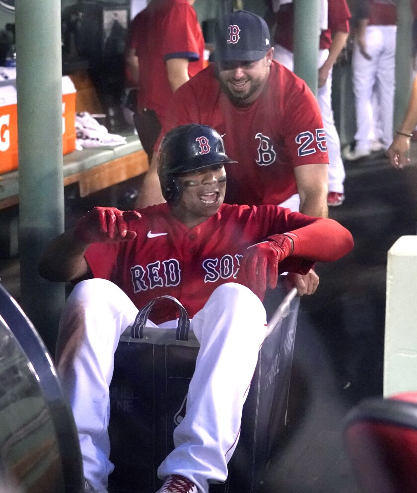 Boston Red Sox's Rafael Devers is pushed through the dugout in a laundry cart by Kevin Plawecki as they celebrate his solo home run during the third inning of the team's baseball game against the Philadelphia Phillies at Fenway Park, Friday, July 9, 2021, in Boston. (AP Photo/Elise Amendola)