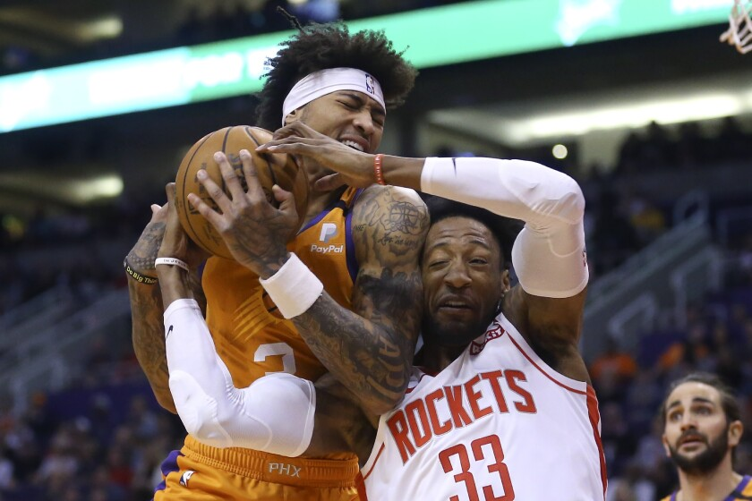 Phoenix Suns forward Kelly Oubre Jr., left, pulls a rebound away from Houston Rockets forward Robert Covington (33) as Suns guard Ricky Rubio, right, looks on during the first half of an NBA basketball game Friday, Feb. 7, 2020, in Phoenix. (AP Photo/Ross D. Franklin)
