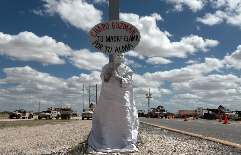 """A member of Los Angeles Mensajeros holds a sign reading in Spanish """"Chapo Guzman, your only mother prays for your soul"""" outside the prison where Guzman is being held in Ciudad Juarez, Mexico."""