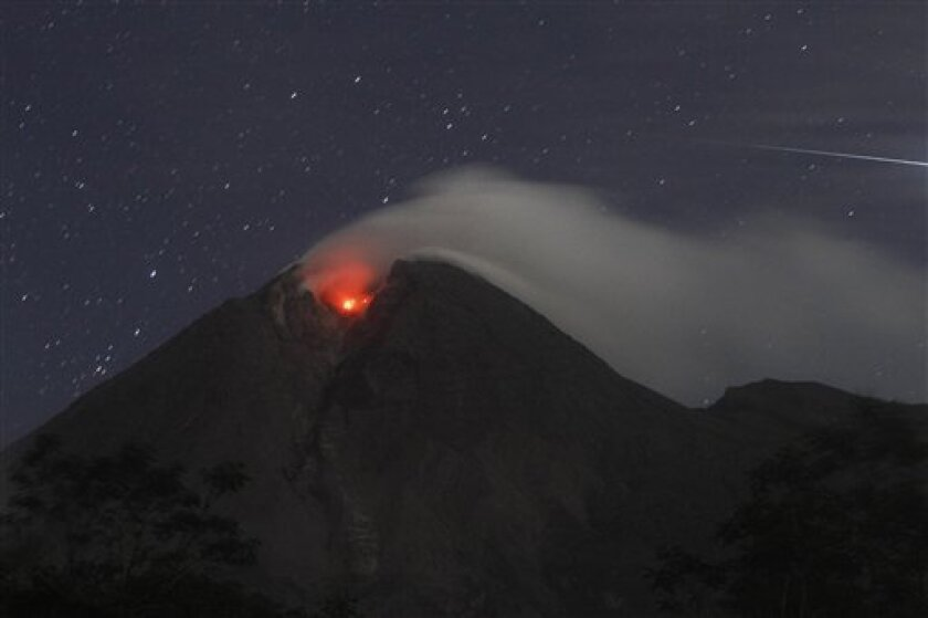 Mount Merapi spews volcanic smoke as seen from Deles, Indonesia, early Monday, Nov. 1, 2010. Indonesia's most volatile volcano unleashed its most powerful eruption in a deadly week Monday, spewing searing clouds of gas and debris thousands of feet (meters) into the air. There were no immediate reports of new casualties. (AP Photo/Irwin Fedriansyah)