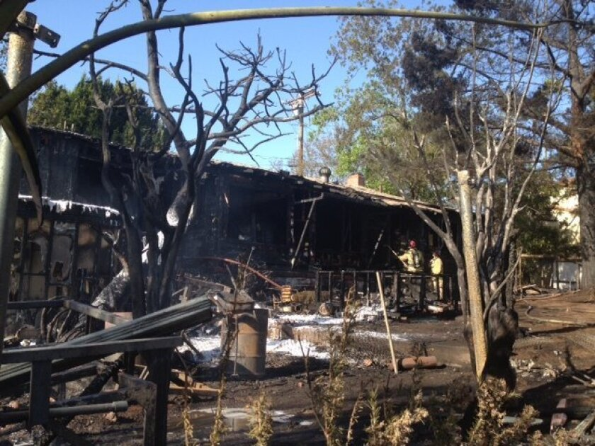 Firefighters clean up after a fire destroyed a home on Dillion Drive in La Mesa Friday.