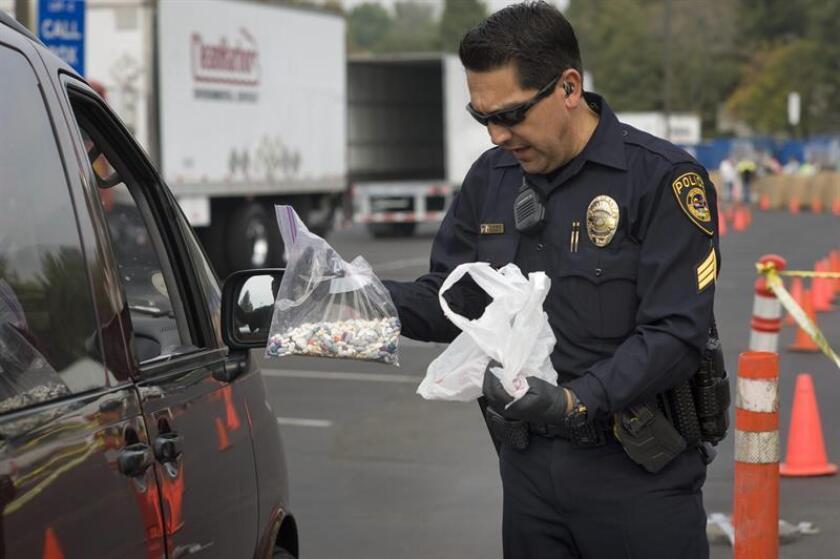 El sargento Robert Sánchez recibe en el estacionamiento del Colegio Comunitario Southwestern de Chula Vista, California (EEUU), medicamentos controlados no utilizados en los hogares que son entregados en el marco de una campaña para controlar la creciente tendencia entre los jóvenes de ingerir analgésicos que se encuentran en los botiquines de las casas. EFE/Archivo