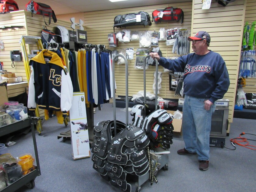 Jim Healey, an owner of Berry's Athletic Supply, looks over some items at the store in its new spot on Lemon Grove Avenue.