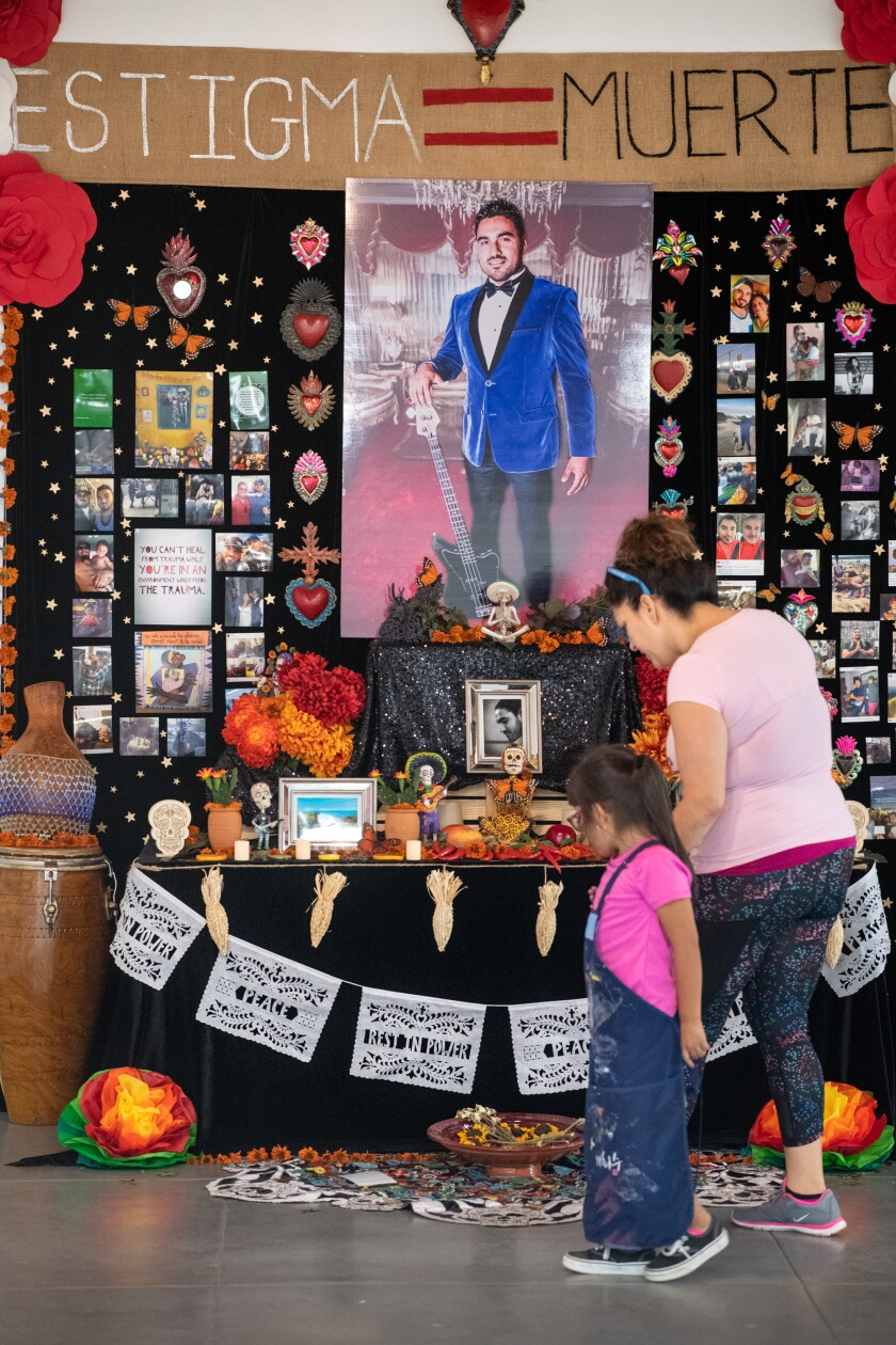 "Lorena Lopez and Maria Bustamante Morales, 4, look at the Day of the Dead ""Altar for Carlos Zaragoza"" at Self Help Graphics & Art."