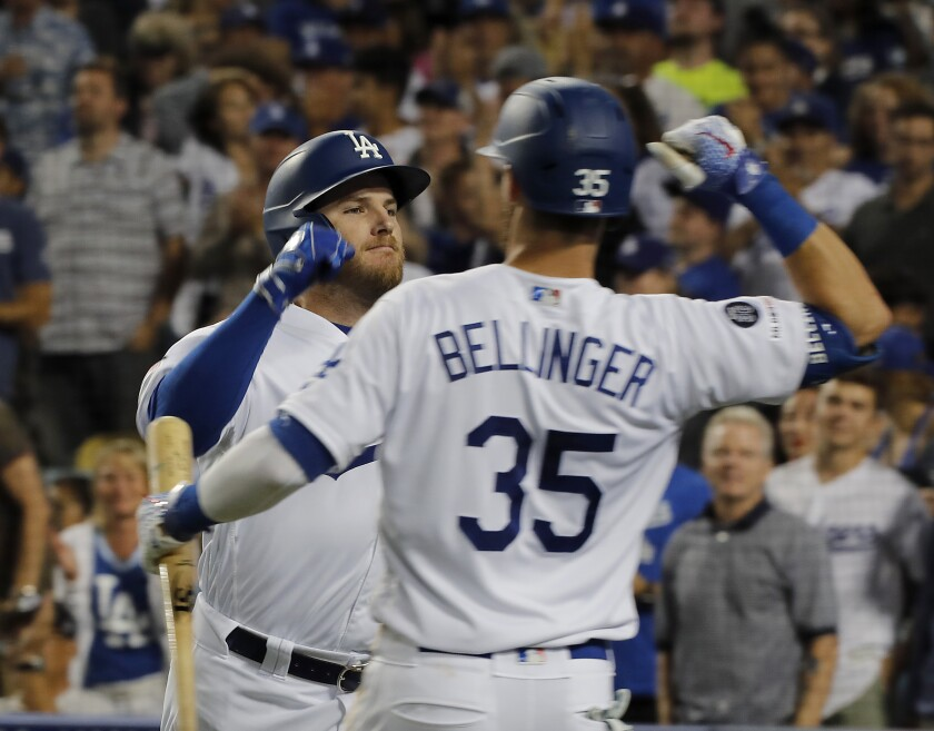 Dodgers third baseman Max Muncy, left, is congratulated by teammate Cody Bellinger.