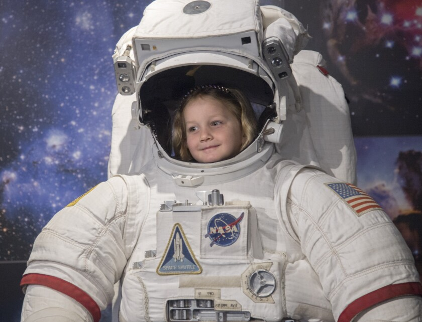 Faith Linenberger, 5, tries on a space suit at the Columbia Memorial Space Center in Downey.