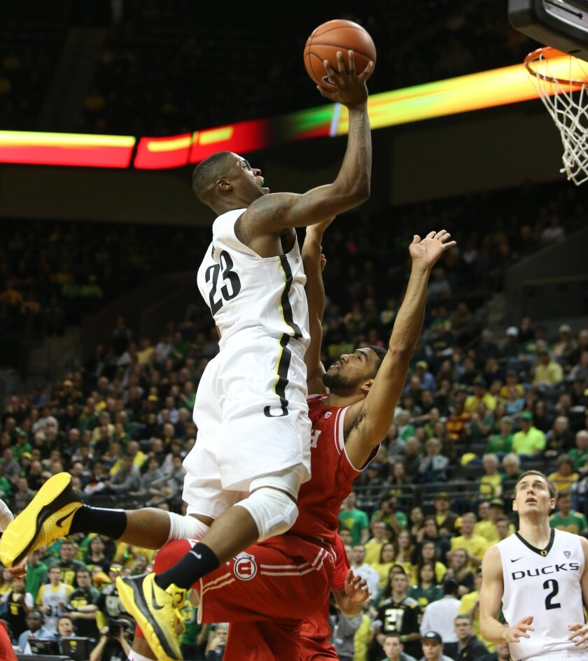 Oregon's Elgin Cook, left, drives over Utah's Isaiah Wright for a layup and a foul call during the first half of an NCAA college basketball game Sunday, Feb. 7, 2016, in Eugene, Ore. (AP Photo/Chris Pietsch)
