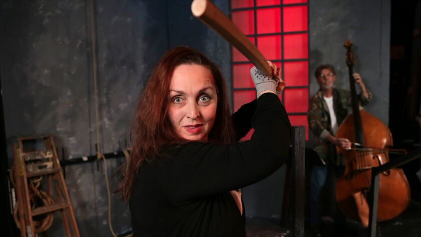 """Linda Libby plays the Poet and bassist Gunnar Biggs plays The Muse in """"An Iliad"""" at New Village Arts Theatre in Carlsbad. Libby holds a Japanese bokken sword she uses in the play."""