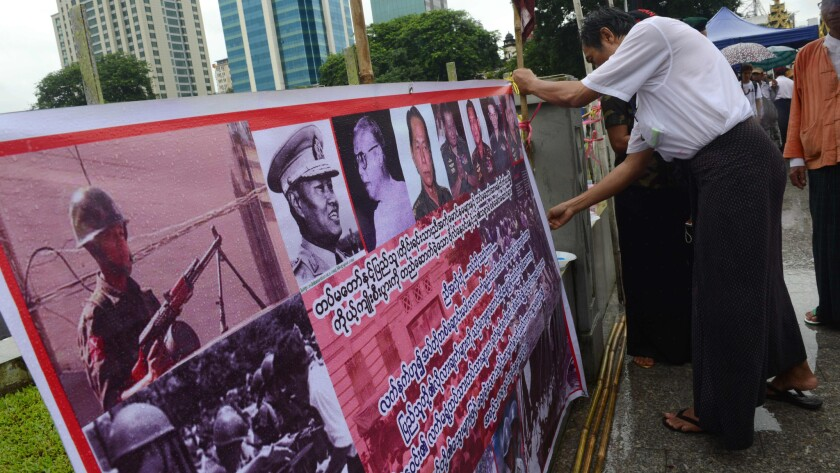 An activist displays a banner bearing portraits of military junta leaders at a Yangon rally to mark the 28th anniversary of the Aug. 8, 1988, democracy uprising.