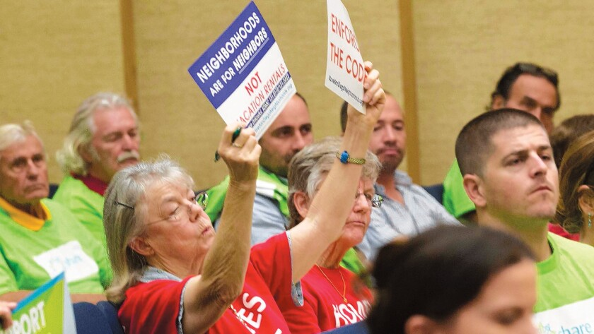 A woman holds up two signs protesting short-term vacation rentals during a San Diego City Council meeting last summer.