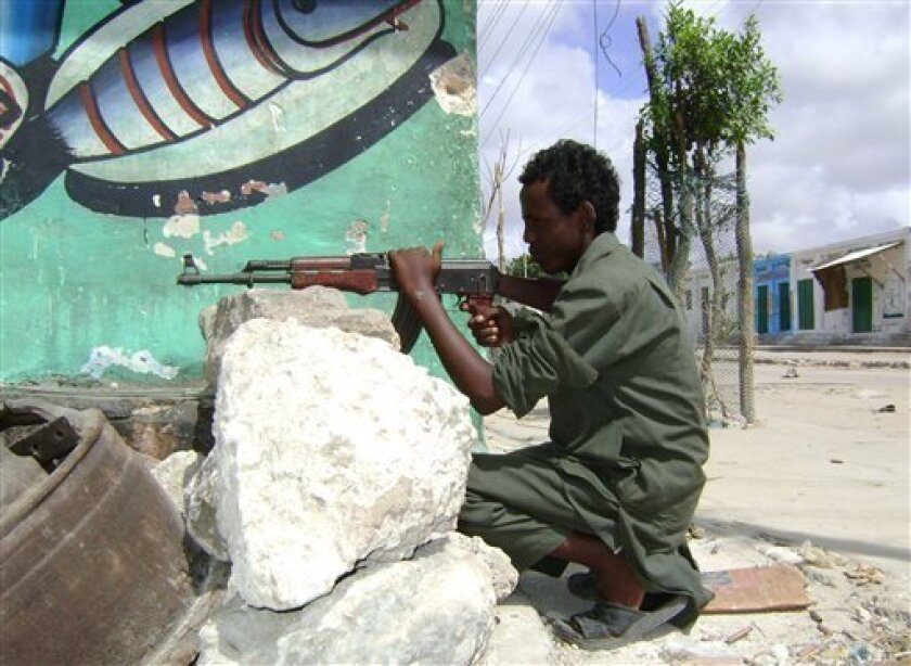 An Islamic fighter take up positions near the presidential palace, during clashes with pro-government forces in the Somali capital, Mogadishu Thursday, May 14, 2009. Islamic insurgents and pro-government forces were firing mortar rounds at each other near the presidential palace in Somalia's capital in the third day of violence this week.(AP Photo/Farah Abdi Warsameh)