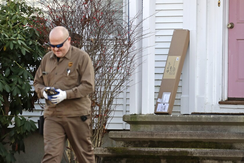 """In this Nov. 26, 2019, photo a UPS man delivers a package to a residence in North Andover, Mass. """"Cyber Monday"""" is still holding up as the biggest online shopping day of the year, even though the same deals have been available online for weeks and the name harks back to the days of dial-up modems. (AP Photo/Elise Amendola)"""
