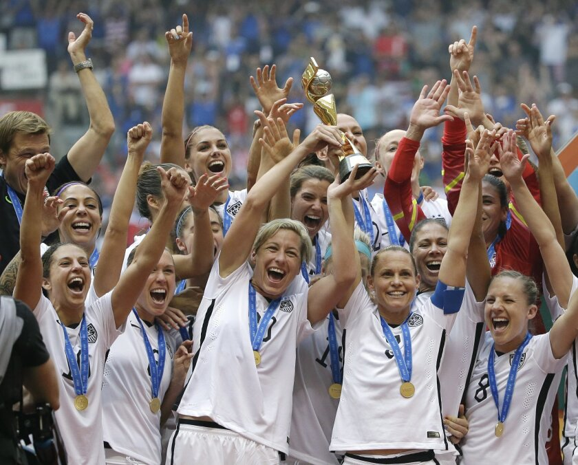 FILE - In this July 5, 2015, file photo, the United States Women's National Team celebrates after they beat Japan 5-2 in the FIFA Women's World Cup soccer championship in Vancouver, British Columbia. The U.S. Soccer Federation has asked that that the Equal Employment Opportunity Commission dismiss