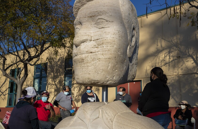 People in masks gather outdoors near a sculpture.