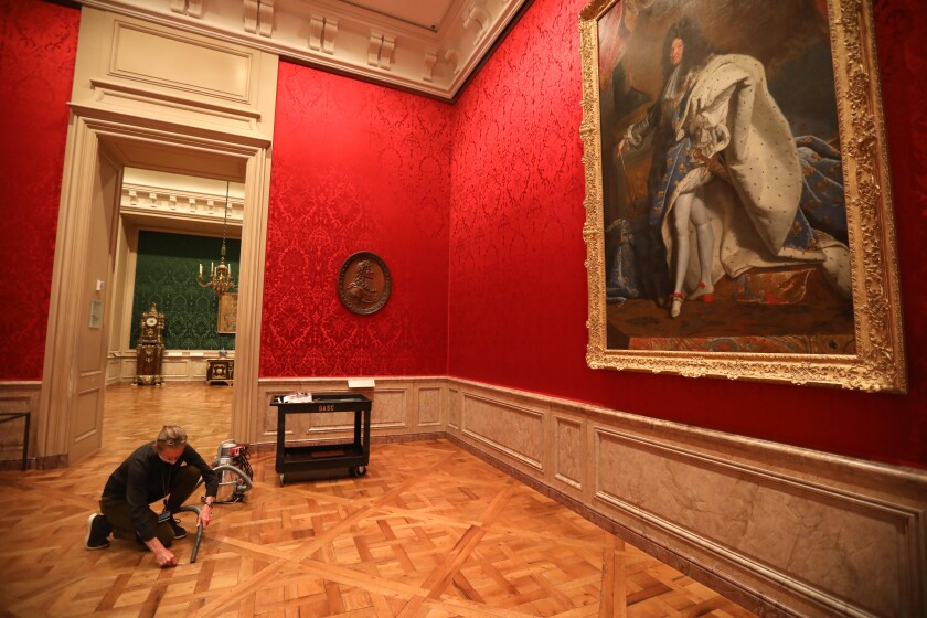 A woman bends to use a vacuum beneath the watchful eye of a portrait