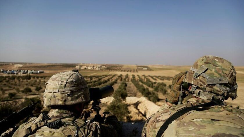 American troops look out in February toward the border with Turkey from a small outpost near the town of Manbij in northern Syria.