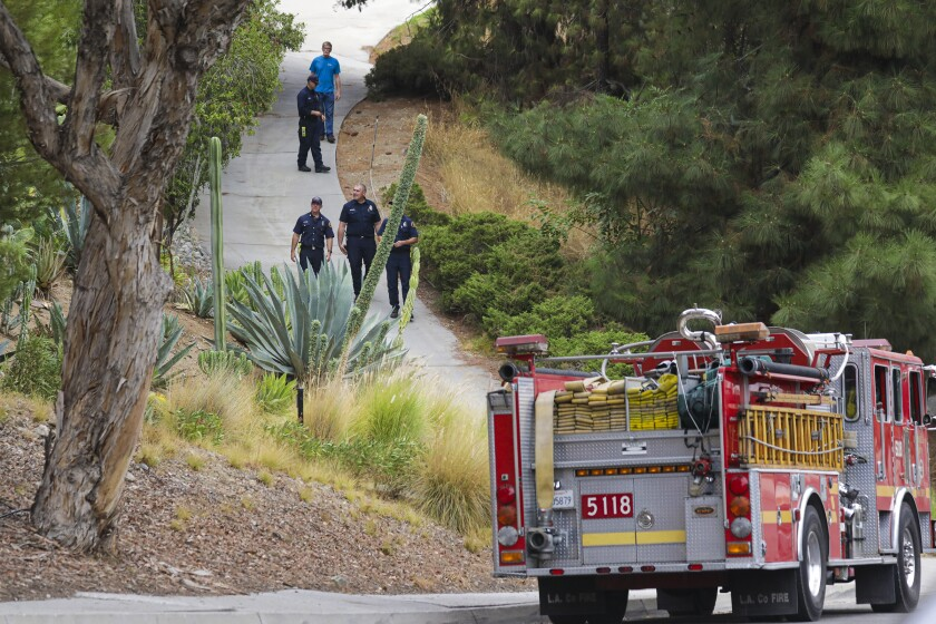 An L.A. County fire protection crew surveys a residential area in Duarte on Tuesday amid a threat from the Bobcat fire.