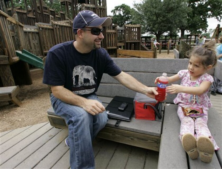 Greg Strange, left, is shown with his daughter Lauren Strange, 3, at Unity Park in Highland Village, Texas, Monday, May 4, 2009. Strange brought his children and a neighbors child to the park because the older children's school is closed as a precaution against swine flu. (AP Photo/Donna McWilliam)