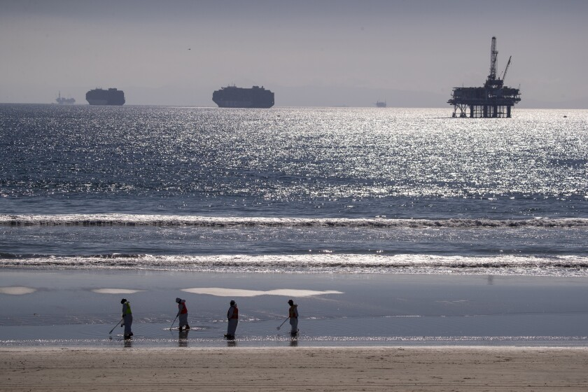Container ships and an oil derrick line the horizon as environmental oil spill cleanup crews search the beach