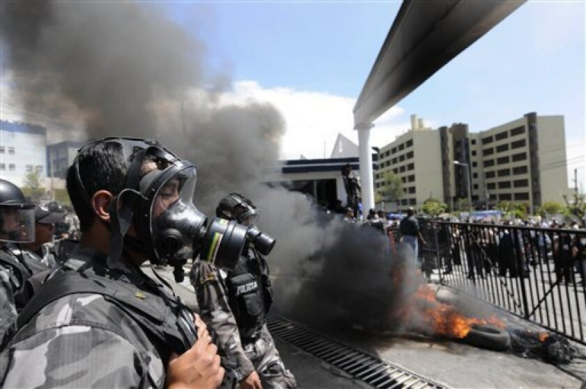 Protesting police burn tires at the entrance of their police base in Quito, Ecuador, Thursday Sept. 30, 2010.  The government declared a state of siege Thursday after rebellious police, angered by a law that cuts their benefits, shut down airports and blocked highways in a nationwide strike. (AP Ph