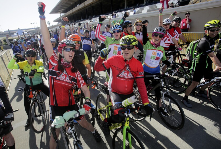 Red Riders Rich Poser, center, and Carmen Ostermeier, left, get psyched up at the start of the 32-mile bike route of the Tour De Cure on Saturday, starting at the Del Mar Fairgrounds, to raise awareness and money to fight diabetes.
