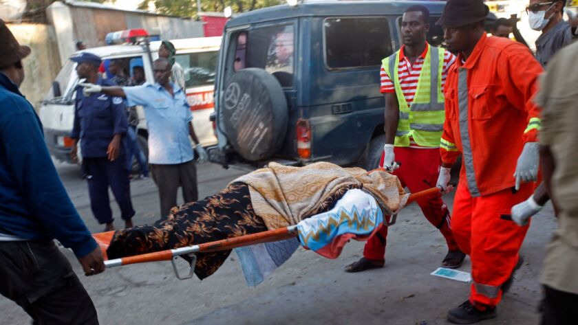 Crews carry a body after an explosion and siege at a Mogadishu hotel.