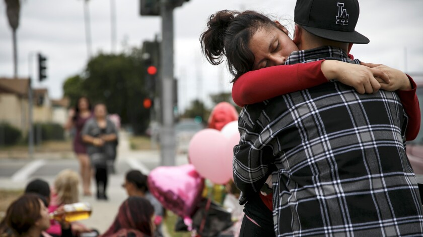 Miriam Ambriz gets a hug as she mourns the loss of her sister Cynthia Ambriz, 19, who was shot and killed in Carson on Saturday.
