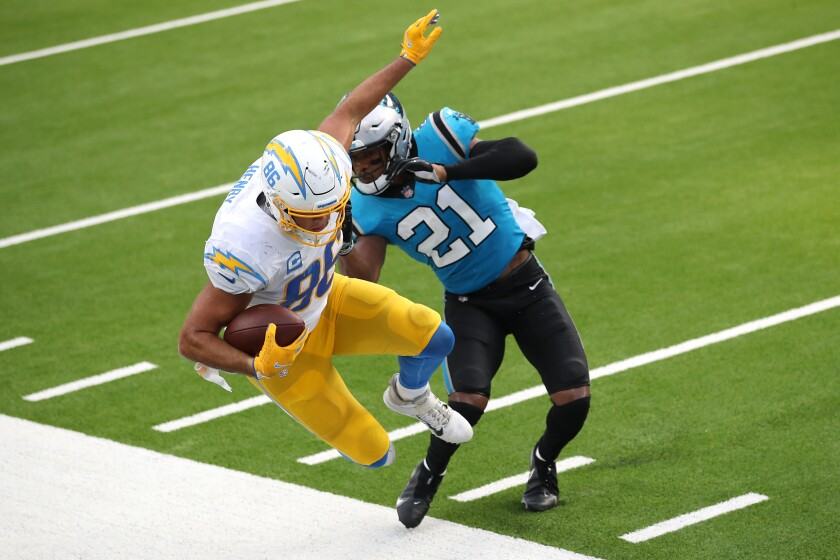 Jeremy Chinn of the Carolina Panthers pushes Hunter Henry of the Los Angeles Chargers out of bounds on a pass play Sunday.