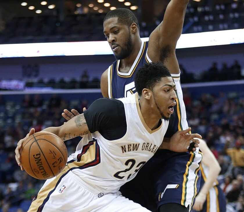 New Orleans Pelicans forward Anthony Davis (23) drives past Utah Jazz forward Derrick Favors (15) during the first half of an NBA basketball game in New Orleans, Wednesday, Feb. 10, 2016. (AP Photo/Tyler Kaufman)