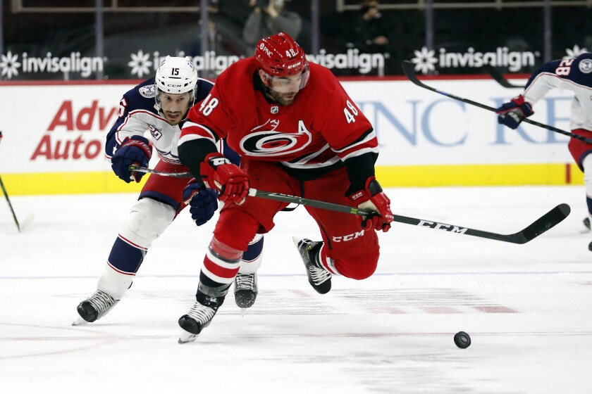 Carolina Hurricanes' Jordan Martinook (48) skates away from Columbus Blue Jackets' Michael Del Zotto (15) with the puck during the second period of an NHL hockey game in Raleigh, N.C., Monday, Feb. 15, 2021. (AP Photo/Karl B DeBlaker)