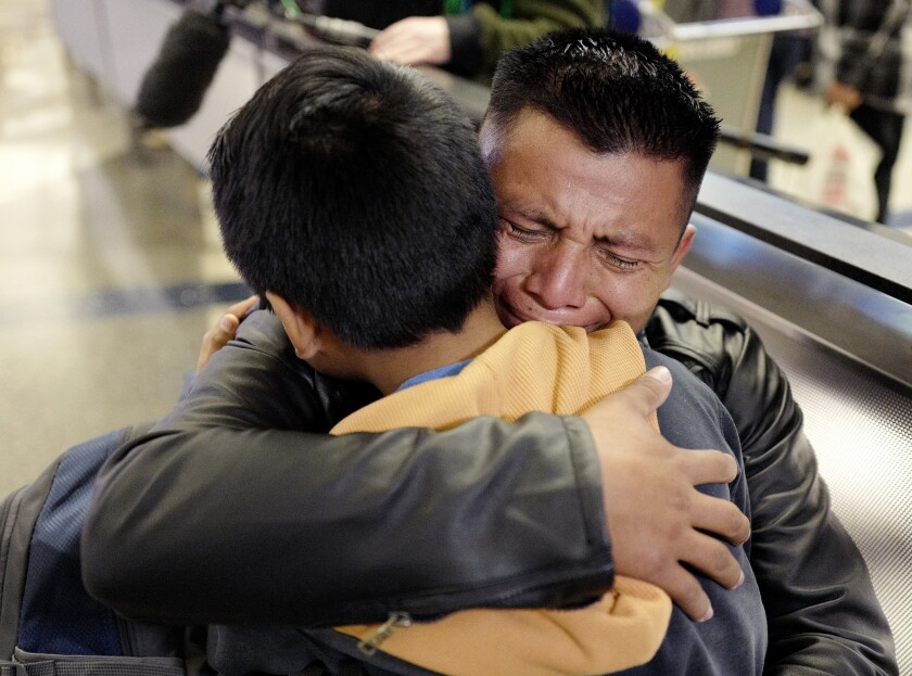 David Xol of Guatemala hugs his son Byron, 9, at Los Angeles International Airport