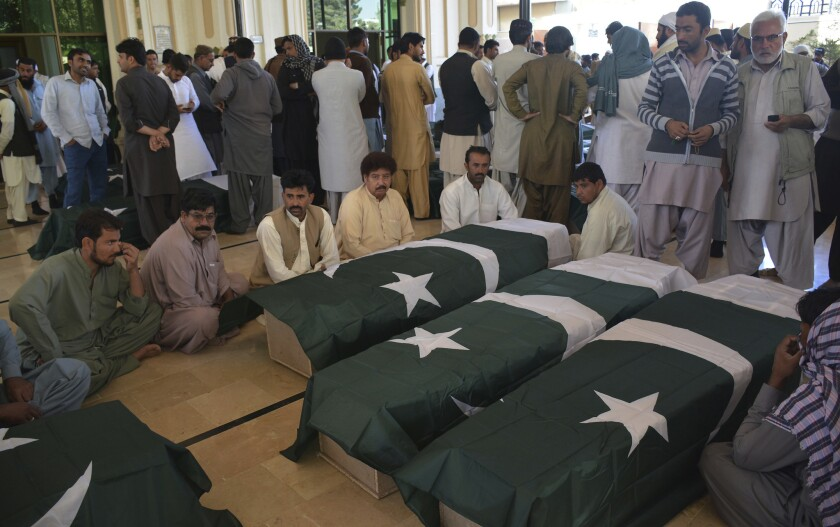 People wait to receive the bodies of family members who died in an attack on the Police Training Academy in Quetta, Pakistan. Militants wearing suicide vests stormed the Pakistani police academy overnight, killing dozens of people, mostly police cadets and recruits.