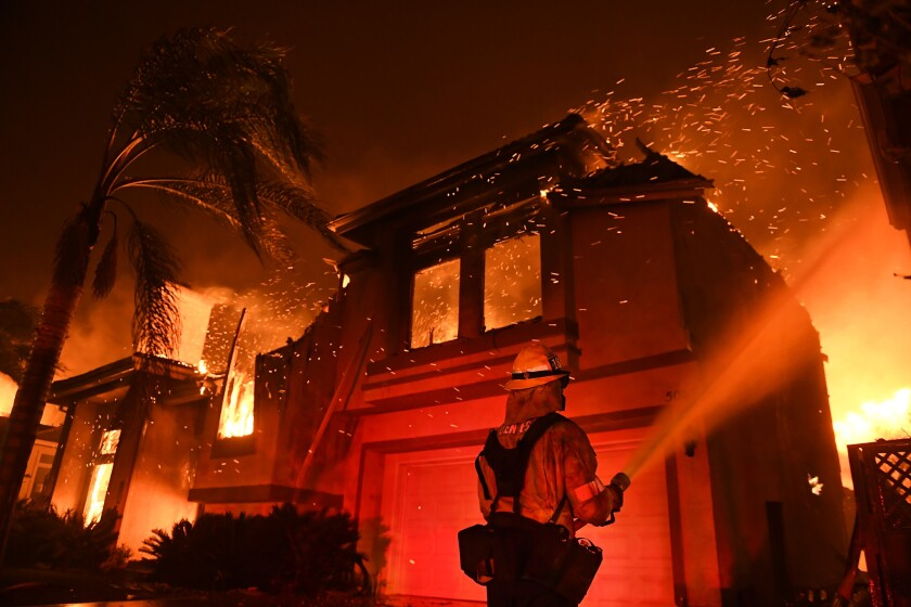 A firefighter battles the flames of the Woolsey fire in an Oak Park neighborhood in the early morning of Nov. 9.