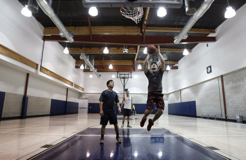 Gilbert Martin shoots as he, Meng Lim, left, and Cory Dela Cruz play in an indoor basketball court at the Alexandria.