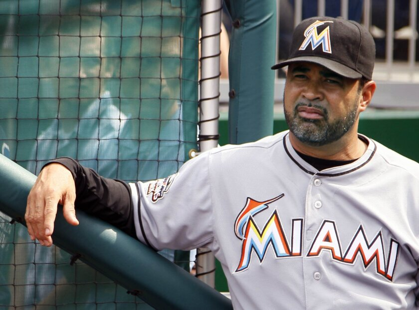 FILE - In this Friday, Aug. 3, 2012 file photo, Miami Marlins manager Ozzie Guillen waits in the dugout before the first baseball game of a doubleheader against the Washington Nationals in Washington. Ozzie Guillen, who led the Chicago White Sox to the 2005 World Series title, has been hired to man