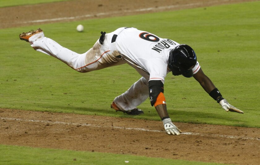 Miami Marlins batter Dee Gordon loses his balance and goes to the turf after unsuccessfully bunting in the eighth inning of an opening day baseball game against the Atlanta Braves in Miami, Monday, April 6, 2015. The Braves won the game 2-1. (AP Photo/Joe Skipper)