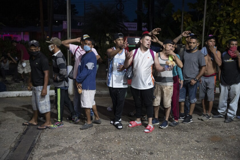 Migrants from Honduras stand in line waiting for aid during their journey to the United States-Mexican border, in Morales, Guatemala, Thursday, Oct. 1, 2020. Honduran migrants hoping to reach the U.S. entered Guatemala on foot Thursday, testing the newly reopened frontier that had been shut due to the new coronavirus pandemic. (AP Photo/Moises Castillo)