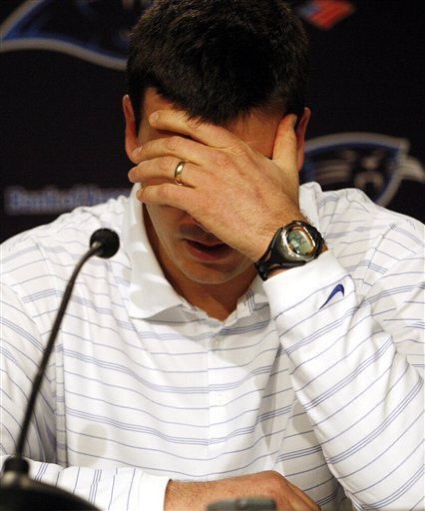 An emotional Jake Delhomme covers his face during a news conference where the former starting quarterback discussed being cut from the Carolina Panthers during a press conference in Charlotte, N.C. Friday, March 5, 2010. (AP Photo/Nell Redmond)